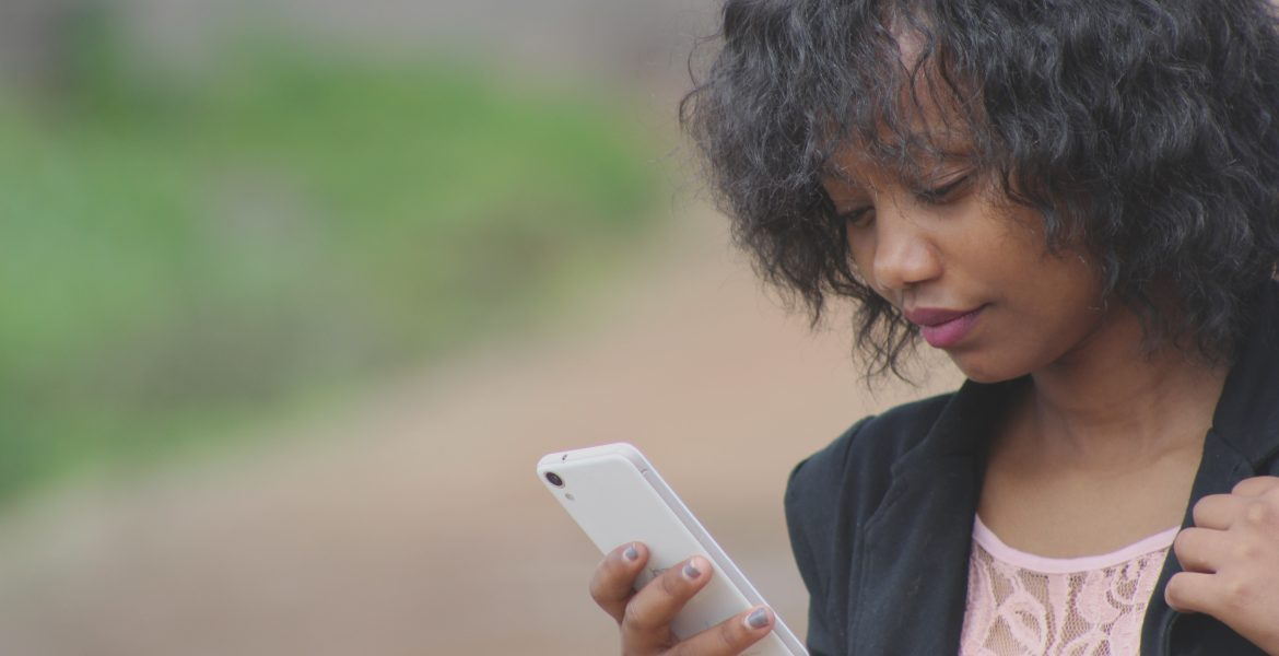 woman looking for signal because she needs a cellular signal booster